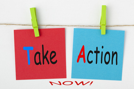 Take Action Now written on color notes with wooden pinch on white background. Business Concept. Imagens