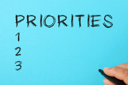 Hand writing Priorities with marker on a blue background. Set Priorities Concept.
