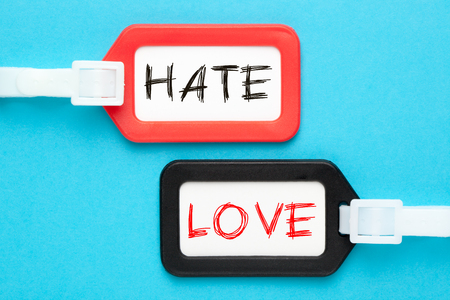 Hate vs Love written on luggage tags on blue background. Business concept.