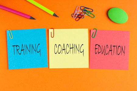 Training, Coaching and Education written on color notes with and office supplies. Business Concept. 스톡 콘텐츠