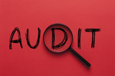 AUDIT written on red background and magnifying glass. Business concept. Stock Photo
