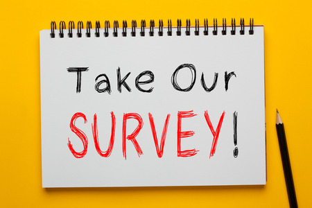 Take Our Survey! written on notepad with pencil on yellow background. Business concept.