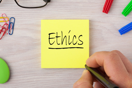 Ethics handwriting on note with marker pen and glasses. Business Concept. Stock Photo