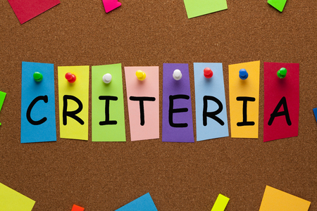 Word CRITERIA written on colorful stickers pinned on cork board.