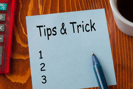 Tips and Trick written on note with pen a side, cup of coffee and calculator. Reklamní fotografie