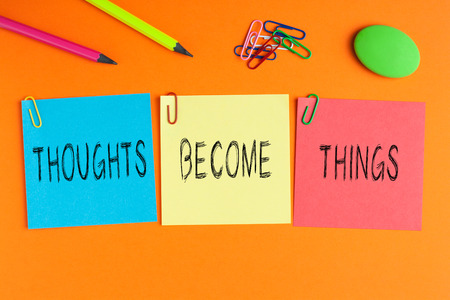 THOUGHTS BECOME THINGS written on color notes with and office supplies. 스톡 콘텐츠