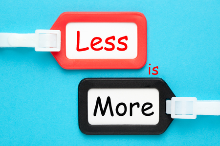 Less is more written on luggage tags on blue background. Business concept.