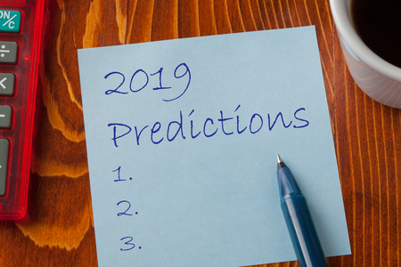 2019 Predictions written on note with pen a side, cup of coffee and calculator. Foto de archivo