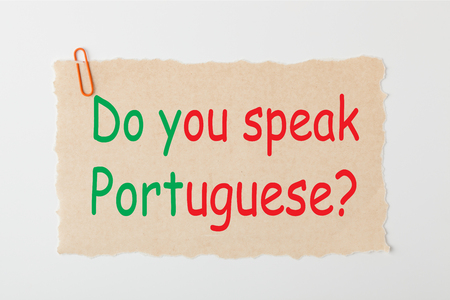 Do you speak Portuguese question writen on old paper with paperclip on white background. language concept.