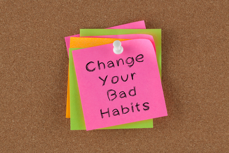 Change Your Bad Habits written on colorful note pinned on cork board. 版權商用圖片