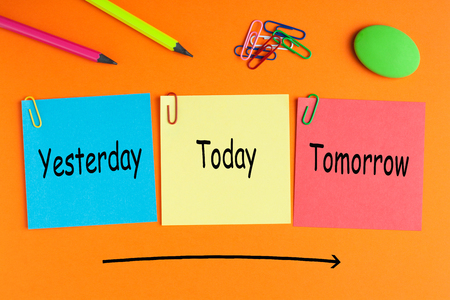 Today, yesterday and tomorrow words on notes pasted on orange background with a big arrow and office supplies. Business concept. Stock Photo