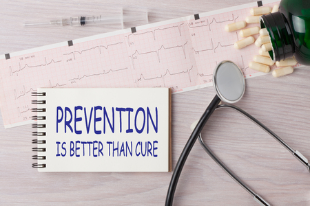Lepiej zapobiegać niż leczyć napisane na zeszycie za pomocą stetoskopu, strzykawki i pigułek. Pojęcie medyczne.