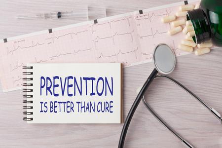 Prevenir es mejor que curar escrito en un cuaderno con estetoscopio, jeringa y píldoras. Concepto médico.