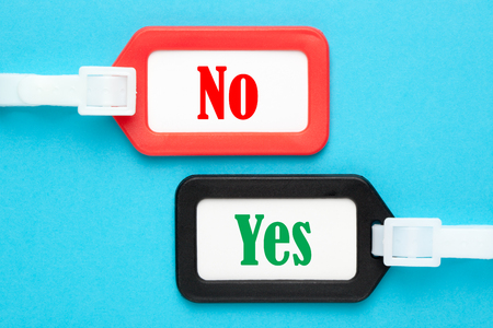 Yes and No written on luggage tags on blue background. Business concept.