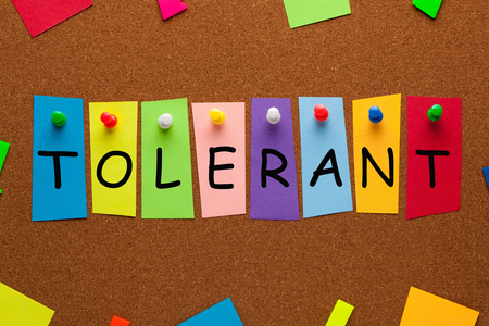 Tolerant word on colorful stickers pinned on cork board. Business concept. Stock Photo
