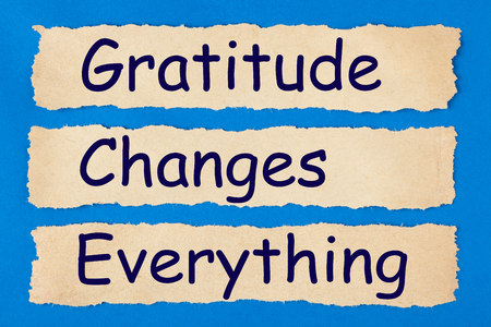 Gratitude Changes Everything written in old torn paper on blue background. Politeness, thanks, gratitude concept Stock Photo