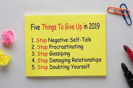 Five Things To Give Up in 2019 written on note with marker pen and various stationery.
