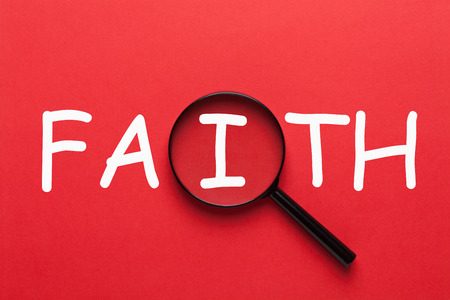 Faith written on red background and magnifying glass. Religion concept. Foto de archivo