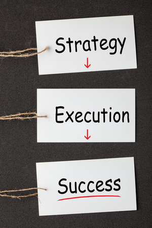 Strategy Execution Success text on white blank paper labels set on the black background. Stock Photo