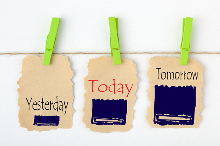 Yesterday, Today and Tomorrow written on old torn paper with clip hanging. Business Concept.