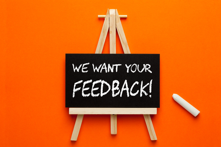 We Want Your Feedback written on blackboard on tripod with chalk. Business concept.
