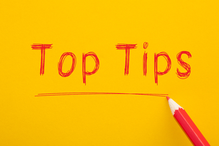 Top Tips word written on yellow background with red pencil. Business Concept. 스톡 콘텐츠