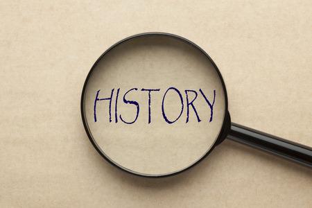 Lupa que se centra en la palabra HISTORIA. Concepto de negocio