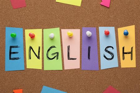 Palabra inglesa escrita en pegatinas de colores clavadas en el tablero de corcho. Concepto de aprendizaje de idiomas Foto de archivo