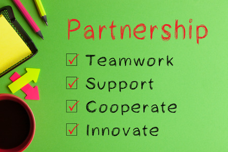 Partnership diagram text messages, cup of coffee and office supplies on green background. Business Concept