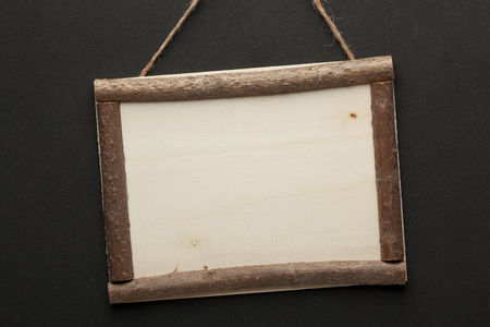 Blank wooden sign hanging on a rope on black background. Empty place for your text Banco de Imagens
