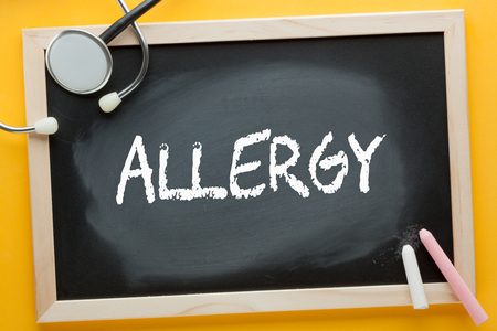 Allergy written on blackboard by color chalks and stethoscope. Medical concept.