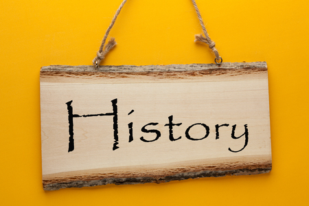History word on wooden sign hanging on a rope on yellow background. Business concept
