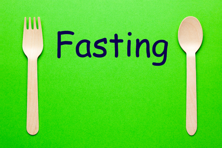Fasting word with spoon and fork on green background. Eat concept.