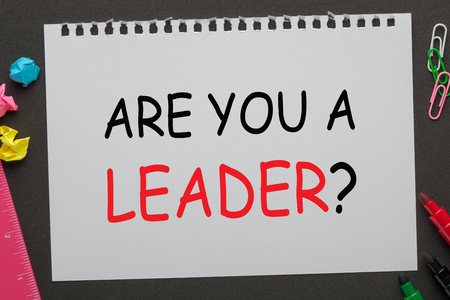 ARE YOU A LEADER question on notebook paper and office supplies on black background. Interview Questions.