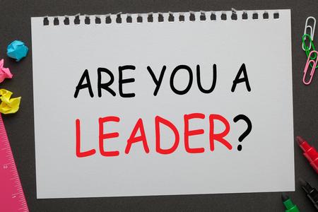 SEI UN LEADER domanda su carta per notebook e forniture per ufficio su sfondo nero. Domande di un'intervista.