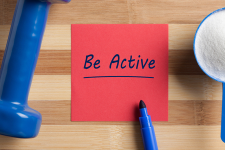 Be Active written on note and scoop with creatine and dumbbell. Concept sport, diet, fitness, healthy eating.