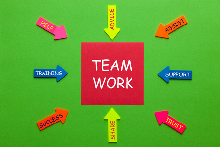 Teamwork with keywords written on notebook and office supplies. Business concept.