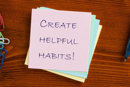 Create helpful habits text on note with pen. Education concept