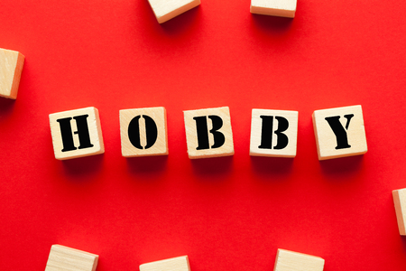 Hobby word written on cubes shape wooden blocks on red background. Business Concept
