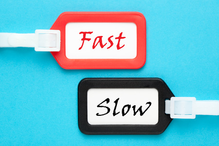 Fast and Slow words on luggage tags on blue background. Business concept