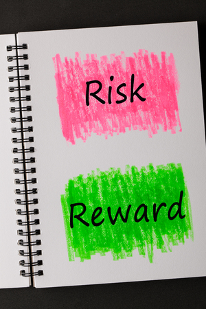 Risk vs Reward words on painted sketchbook in red and green. Business concept. Imagens