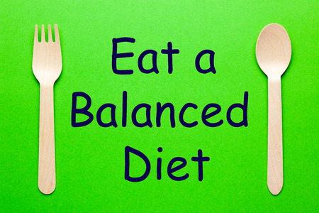 Eat a Balanced Diet with spoon and fork on green background. Healthy diet.