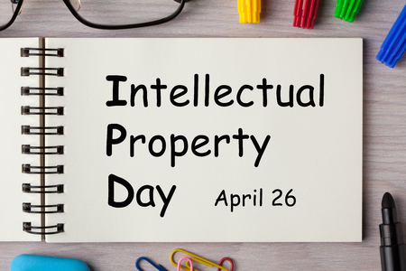 World Intellectual Property Day written on notebook page with marker pen and various stationery. Business concept. Imagens