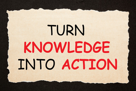 Turn Knowledge Into Action text on old torn paper on black background. Motivation concept
