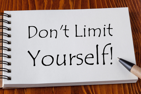 Dont Limit Yourself text on notebook with pen aside on wooden desk.