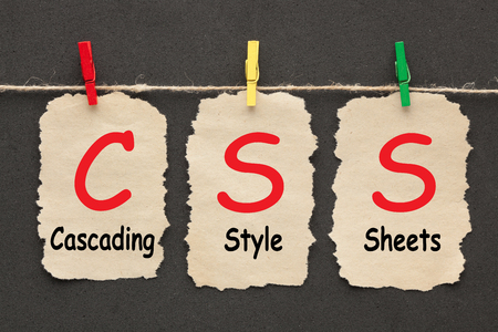 Cascading Style Sheets(CSS) written on set stickers with clip hanging on a rope on black background.