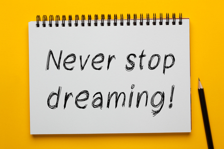 Never Stop Dreaming written on notepad with pencil on yellow background. Business concept. Banco de Imagens