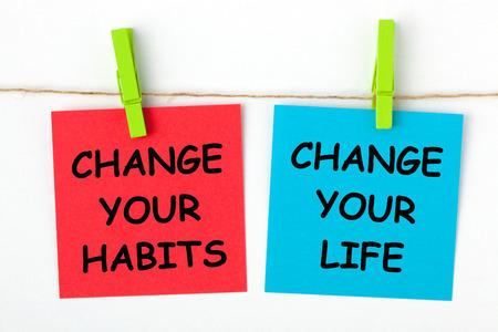 Ändern Sie Ihr Leben, indem Sie Ihre Gewohnheiten ändern Text auf Farbnotizen mit Holzprise geschrieben. Standard-Bild