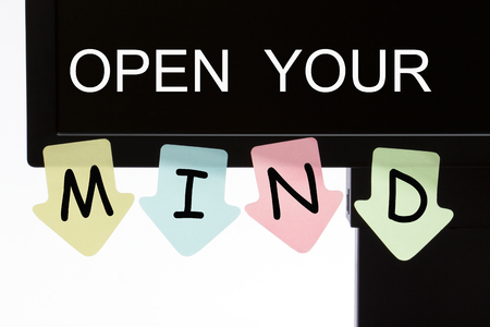 Open Your Mind text on computer display and reminder notes. Business concept.