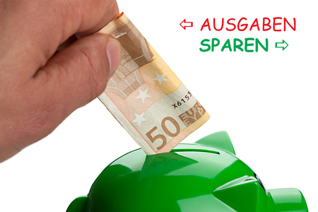 Hand putting banknote on a piggy bank and text Save Spend in German.